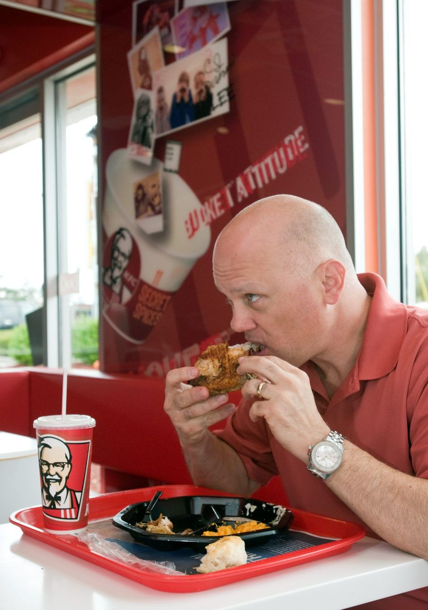** FILE ** Mike Ash of Louisville, Ky., home of the original Kentucky Fried Chicken chain, samples the restaurant's new grilled chicken entree. (Associated Press)