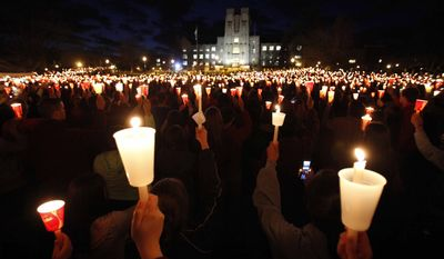 ** FILE ** Students, friends and family hold up candles during a vigil on the campus of Virginia Polytechnic Institute and State University in Blacksburg, Va., on Thursday, April 16, 2009, to mark the second anniversary of the Virginia Tech shootings. (AP Photo/Steve Helber)