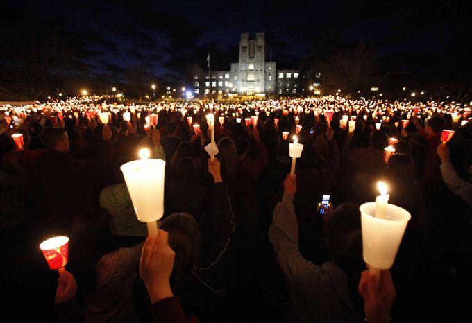 ** FILE ** Students, friends and family hold up candles during a vigil on the campus of Virginia Polytechnic Institute and State University in Blacksburg, Va., on Thursday, April 16, 2009, to mark the second anniversary of