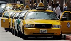 ASSOCIATED PRESS Taxis wait for fares across the street from a large hotel in downtown Los Angeles. The city's Hail-A-Taxi effort is off to a slow start, raising questions whether Angelenos are too attached to their cars.