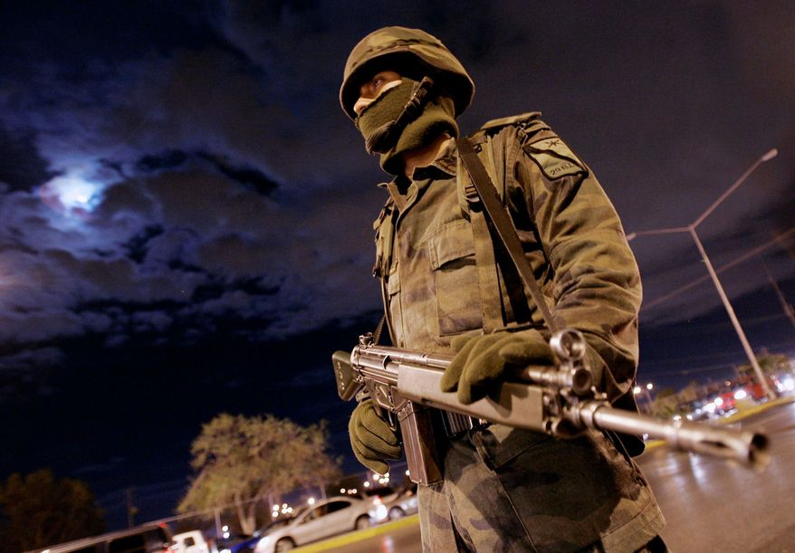 A Mexican soldier stands guard near a U.S.-Mexico border crossing during an operation in Ciudad Juarez, Mexico, in early March. A federal report, released following a Freedom of Information Act lawsuit, says unauthorized border crossings by Mexican soldiers and police more than tripled in 2008. (Associated Press)