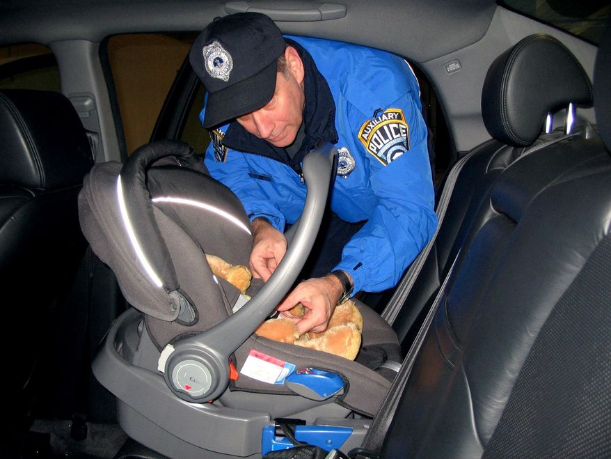 A furry friend helps Auxiliary Police Cpl. James Murphy demonstrate harness use in a child-safety seat.