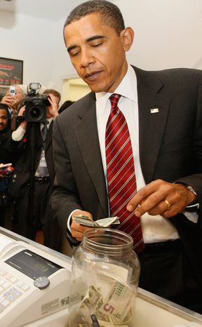 President Barack Obama drops a five dollar bill into the tip jar as he and Vice President Joe Biden, not pictured, make an unannounced visit to Ray's Hell Burger in Arlington, Va., to have lunch, Tuesday, May 5, 2009. (AP Photo/Charles Dharapak)