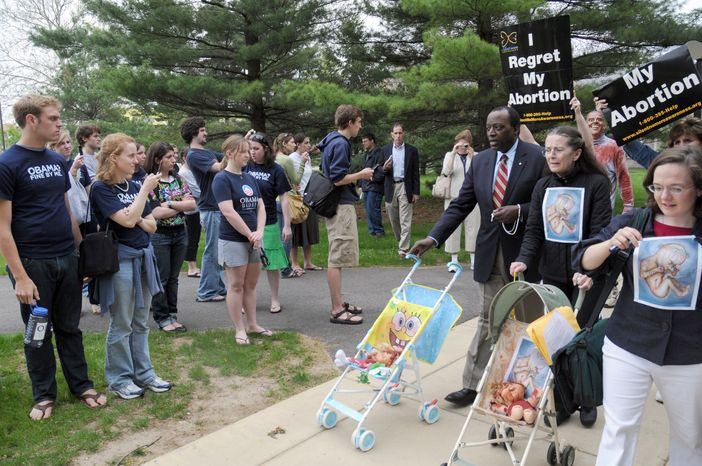 **FILE** In this photo taken May 8, 2009, anti-abortion protestors led by Alan Keyes cross the path of pro-Obama Notre Dame students in South Bend, Ind. (Associated Press)