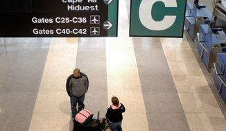 Passengers stand in a near-empty terminal at Logan International Airport in Boston. Flying can be an expensive travel option for families when travelers figure in baggage fees and rental cars.