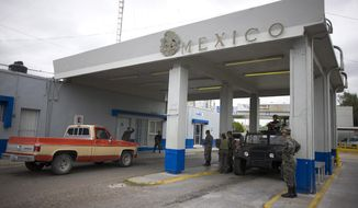 Mexican soldiers check cars at the customs checkpoint in Miguel Aleman, on Mexico's northeastern border with the U.S., Wednesday, March 18, 2009. (AP Photo/Alexandre Meneghini)