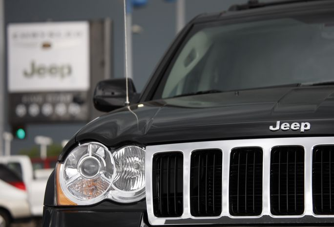 **FILE** In this photo taken Sunday, May 31, 2009, the company sign hangs near an unsold 2009 Grand Cherokee at a Chrysler-Jeep dealership in the south Denver suburb of Englewood, Colo. Chrysler LLC's U.S. sales fell 47 percent in May, but the company