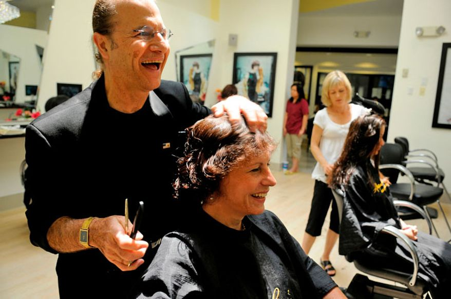 Alexandre de Paris gives a free haircut to Lucia Giordano, 47, of Alexandria, Va., who was fired a few months ago from her Special Events job at Ft. Belvoir. (Mary F. Calvert/The Washington Times)