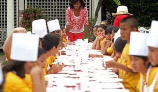 ** FILE ** First lady Michelle Obama talks to students from Bancroft Elementary School in Washington as they wait to eat a meal. (The Washington Times)