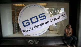 """An advertisement that reads """"all the store on sale"""" runs across the storefront in Caracas, Venezuela, where a drop in oil prices has roughly cut in half the amount of goods the country can afford to import."""