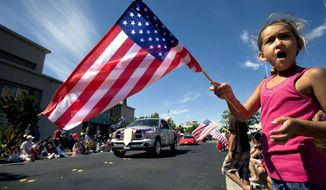 SACRAMENTO BEE STARS AND STRIPES: Aliah Penrod, 6, of Roseville, Calif., waves the American flag during the town's July 4th parade last year. Roseville is just one of many towns that have had to cut back on Independence Day celebrations owing to the recession.