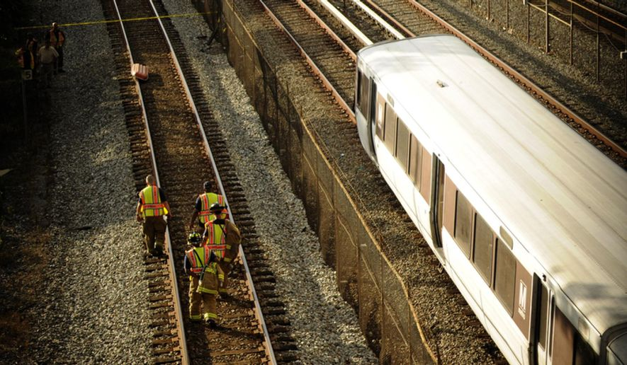 Emergency personnel walk along the tracks at the scene where two Metro red line trains collided.  (Rod Lamkey Jr. / The Washington Times)