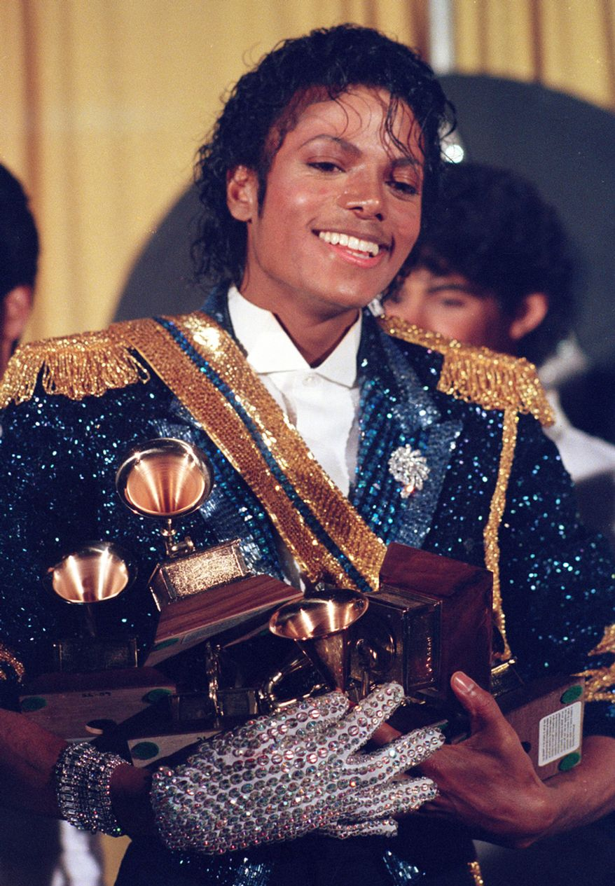 In this Feb. 28, 1984 file photo, Michael Jackson is seen backstage at the 26th annual Grammy Awards in Los Angeles as he poses with the awards he won in eight different categories. (AP Photo/Reed Saxon, file)