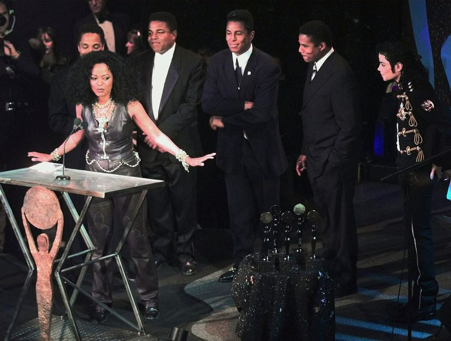 Diana Ross introduces the Jackson 5 as they are inducted into the Rock and Roll Hall of Fame on Tuesday, May 6, 1997, in Cleveland. From left are Marlon, Tito, Jermaine, Jackie and Michael. (AP Photo/Amy Sancetta)
