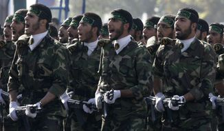 FILE - This Sept. 21, 2008, file photo shows Iranian basij paramilitary volunteers, affiliated to the elite Revolutionary Guard, attending a parade ceremony, marking the 28th anniversary of the onset of the Iran-Iraq war (1980-1988), in front of the mausoleum of the late revolutionary founder Ayatollah Ruhollah Khomeini, just outside Tehran, Iran.