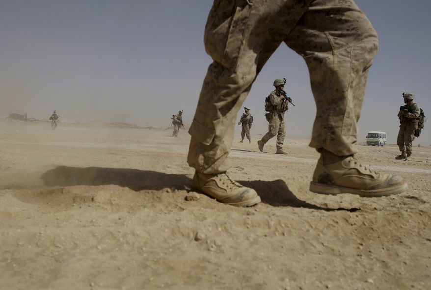 **FILE** U.S. Marines from the 2nd Marine Expeditionary Battalion walk through the sand inside Camp Leatherneck in Afghanistan's Helmand province on June 8, 2009. (Associated Press)