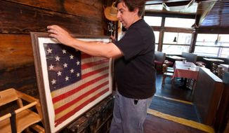 ** FILE ** Silver Spur Saloon proprietor Marc Peagler displays an early 1800s 13-star U.S. flag at his bar in Cave Creek, Ariz., on Friday, June 26, 2009. An Arizona House committee has made dramatic changes to a Senate-passed bill allowing people with concealed weapons permits to carry their firearms into businesses that serve alcohol. Mr. Peagler supports the measure. (AP Photo/Aaron J. Latham)