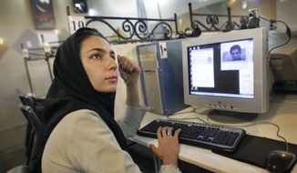 An Iranian woman who declined to give her name uses the Internet in Nikoo Coffeenet internet cafe in the Tadrish bazaar in northern Tehran, Iran, in this June 11, 2009, file photo. (Associated Press) ** FILE **
