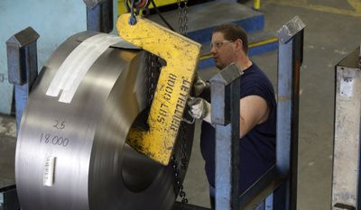 ** FILE ** Derek Jenkins, an employee at Baldor Electric Co., moves a large roll of steel inside the company's factory in St. Louis in June 2009. (AP Photo/Jeff Roberson, File)