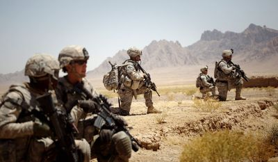 U.S. soldiers from the 5th Striker Brigade patrol near the Sari Ghundi village along the Pakistan-Afghanistan border Monday. The administration is preparing benchmarks to test how effective President Obama's strategies are in Afghanistan and Pakistan amid growing skepticism among Democrats about the wars' prognosis and costs. (Associated Press)
