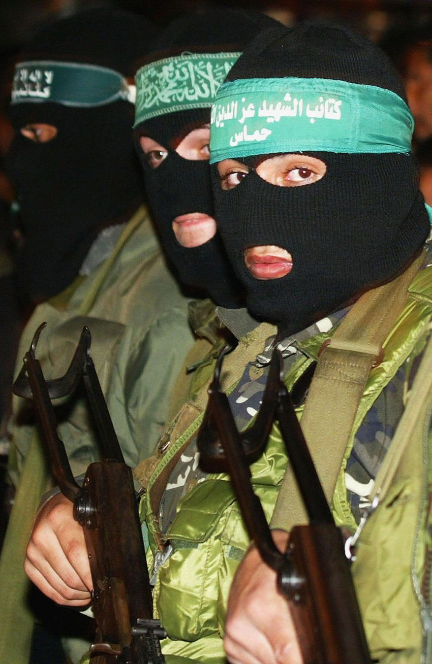 "GAZA CITY, GAZA STRIP -In this file photo, masked Hamas militants march during a demonstration supporting Hamas' Spiritual Leader Sheikh Ahmed Yassin on January 16, 2004, in Gaza City, Gaza Strip. Thousands of Palestinians demonstrated in Gaza Strip towns and refugee camps after the Israeli deputy defense minister stated that ""Yassin is marked for death"" following a suicide bombing that killed three Israeli soldiers and a security officer in Gaza. (Photo by Abid Katib/Getty Images)"
