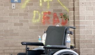 ASSOCIATED PRESS OVERLOOKED: A wheelchair sits outside the main entrance to a nursing home in New Orleans in the wake of Hurricane Katrina.
