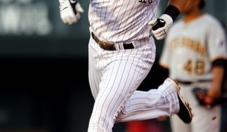 Colorado Rockies' Troy Tulowitzki, front, circles the bases after hitting a solo home run as Pittsburgh Pirates second baseman Delwyn Young, back, looks on in the second inning of a baseball game in Denver on Tuesday, Aug. 11, 2009. (AP Photo/David Zalubowski)