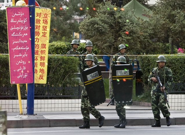 Chinese paramilitary police officers patrol near the People's Square after they closed down the road leading to the square in Urumqi province, Xinjiang, China, Friday, Sept. 4, 2009. Thousands marched through this city in western China after a series of stabbings with hypodermic needles further unnerved residents already jittery over deadly rioting between Han Chinese and Muslim Uighurs. (AP Photo/Andy Wong)