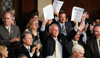 ** FILE ** Rep. Paul Broun, R-Ga., holds up the Republicans version of a health care reform bill, standing with other republicans.  (Allison Shelley / The Washington Times)