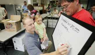 Tim Eyman holds his daughter Riley, 1, in July 2009 while updating a board tallying petition signatures for getting an initiative on the Washington state ballot. Mike Fagan holds the board. Mr. Eyman co-sponsored Initiative 1053 which passed with 66 percent of the vote on Nov. 2, 2010. (Associated Press)