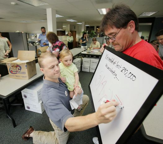 Tim Eyman holds his daughter Riley, 1, in July 2009 while updating a board tallying petition signatures for getting an initiative on the Washington state ballot. Mike Fagan holds the board. Mr. Eyman co-sp