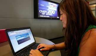 **FILE** Joy Troy checks a Twitter page at the University of Southern California in Los Angeles. (Associated Press)