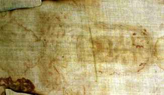 ** FILE **  The Shroud of Turin, a 14-foot-long linen revered by some as the burial cloth of Jesus, is shown at the cathedral in Turin, Italy, in 2000. (Associated Press)