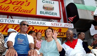 In this file photo from Aug. 22, 2003, comedian Bill Cosby (left) joins Ben Ali (right) and Ali's wife Virginia during a celebration on the 45th anniversary of Ben's Chili Bowl Restaurant in Washington. Ben Ali, founder of the restaurant which became a Washington landmark, died Wednesday at his home in Washington. He was 82. (Associated Press)
