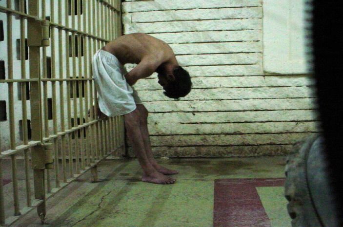 **FILE** This 2003 photo obtained by the Associated Press shows a detainee bent over with his hands on the bars of a prison cell at the Abu Ghraib prison in Baghdad, Iraq. (AP Photo)