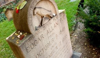 Roses and pennies are placed on the original gravesite of Edgar Allan Poe during a mock funeral held in at Westminster Hall in Baltimore, Md. Sunday, Oct. 11, 2009, to celebrate the bicentennial of his life. (Michael Connor/The Washington Times/File) ** FILE **