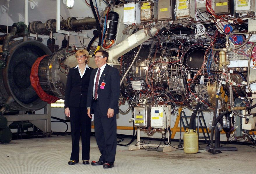 "** FILE ** Jean Lyndon-Rodgers (left), president of GE Aviation, and Mark Rhodes, senior vice president of Rolls- Royce, stand near the F-136 jet engine in Evendale, Ohio, in October 2009. The alternative engine is ""unnecessary"" and may harm the Joint Strike Fighter program, Defense Secretary Robert M. Gates said then."