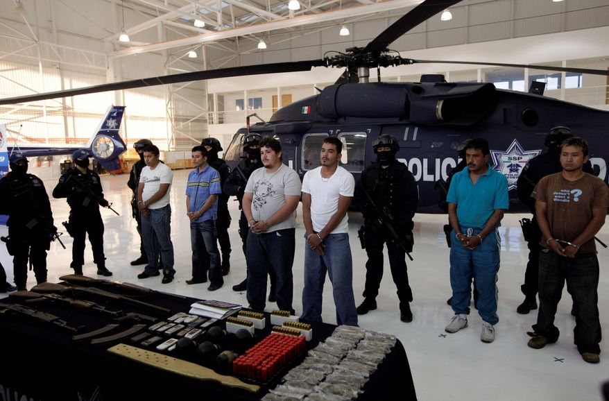 Mexican federal police in Mexico City line up purported members of the violent drug cartel La Familia, detained in a recent police operation, as the U.S. on Thursday announced its own operation against the gang north of the border. (Associated Press)
