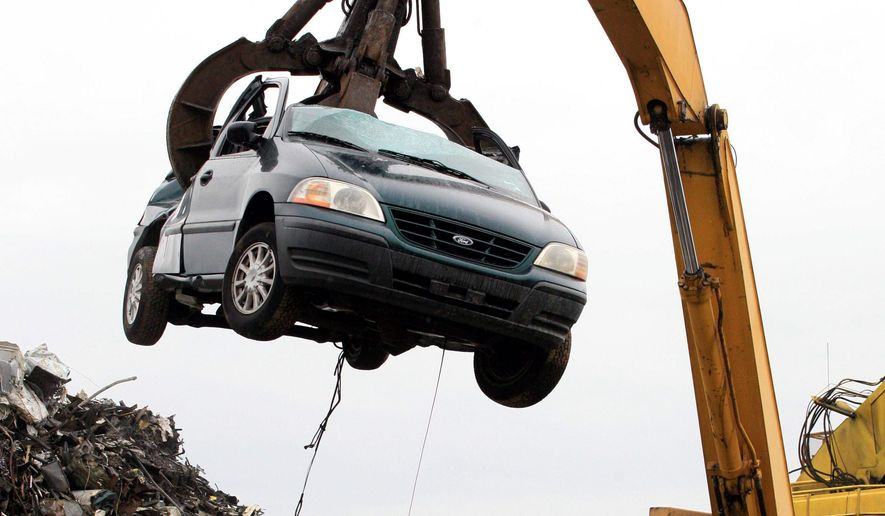 """ASSOCIATED PRESS A crane lifts a clunker at a New York recycling yard as auto recyclers report a torrent of cars that must be properly disposed of before the government's deadline, which they say is not possible after Washington extended the popular """"cash for clunkers"""" program."""