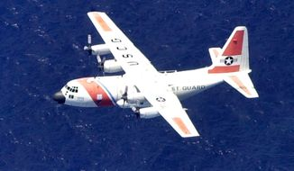 **FILE** In this August 2, 2003 photo, a U.S. Coast Guard C-130 aircraft flies over the waters off the southwest coast of Eleuthera in the Bahamas. (Associated Press)