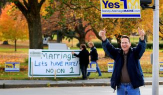 In this Nov. 4, 2009 photo, Joseph Skinner urges passing motorists to support Question 1 on the Maine ballot, which would repeal a lawmaker-passed law legalizing gay marriage. Gay marriage supporters Ann DiMella and Suzanne Blackburn post their own sign urging people to reject the referendum. (Associated Press/File)