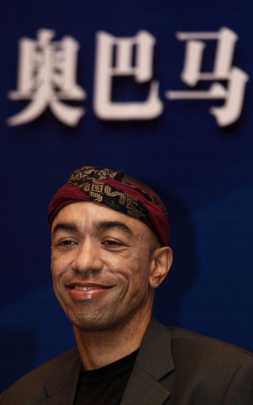 """Mark Ndesandjo, one of President Barack Obama's half-siblings, attends a news conference for his new book """"Nairobi to Shenzhen"""" with the background written """"Obama"""" in Chinese characters, in Guangzhou, southern city of China Wednesday, Nov. 4, 2009. (AP Photo/Kin Cheung)"""