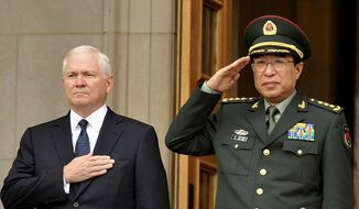 **FILE** Defense Secretary Robert M. Gates (left) and Gen. Xu Caihou, vice chairman of China's Central Military Commission, listen to national anthems at an Oct. 27, 2009, welcome ceremony at the Pentagon. (Associated Press)