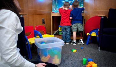 Twins Peter (right) and Daniel Belin look at a fish tank as their mom Jennifer watches at Bethesda's National Naval Medical Center, where the twins' father works. Dr. Eric Belin was referred to the Walter Reed Army Medical Center for his son's treatment by top military physicians.