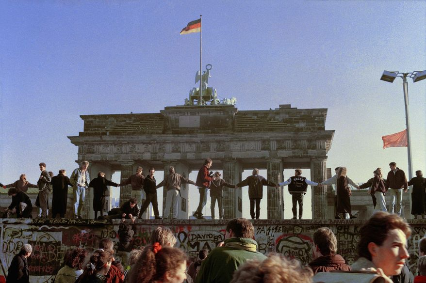East and West Berliners dance together on the top of the Berlin Wall in front of the Brandenburg Gate on Nov. 10, 1989, to celebrate the opening of the border between East and West Germany. Built in 1961 of concrete topped by barbed wire, the wall dividing Berlin became one of the most powerful symbols of the Cold War. (Associated Press)