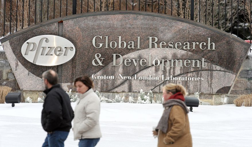 **FILE** In this photo from Jan. 13, 2009, Pfizer employees walk past a sign at the Pfizer Global Research and Development facility in Groton, Conn. Pfizer Inc., the world's biggest drug company, on Nov. 9 said it is closing six of its 20 research facilities, reorganizing others, and cutting the jobs of roughly 15 percent of its scientists and support staff. (Associated Press)
