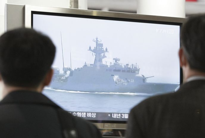 South Koreans watch a television screen showing undated file footage of a South Korean Navy ship near the disputed waters off South Korea's west coast, at a railway station in Seoul on Tuesday, Nov. 10, 2009. The two Koreas briefly exchanged naval fire Tuesday along their disputed western sea border, with a North Korean ship suffering heavy damage before retreating, South Korean military officials said. (AP Photo/Ahn Young-joon)