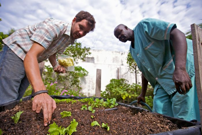 In this November 2009 file photo, a Peace Corps volunteer helps a Senegalese man garden.