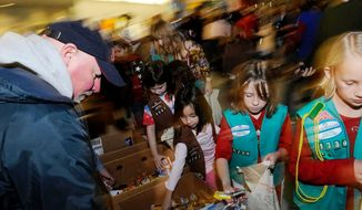 ** FILE ** Junior Girl Scouts from Troop 1739 in Crofton, Md., help gather bags of treats to give out to the troops returning home from war at BWI Airport. (Rod Lamkey Jr/The Washington Times)