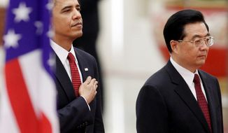 **FILE** President Obama stands at attention with Chinese President Hu Jintao at the Great Hall of the People in Beijing on Nov. 17, 2009. (Associated Press)